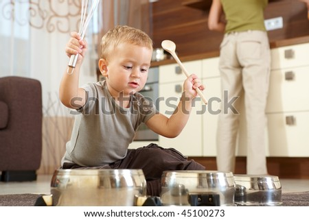 Little boy sitting on carpet in kitchen playing with cooking pots, mother preparing food in background. - stock photo