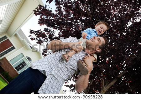 Little boy sitting on father's shoulders - stock photo