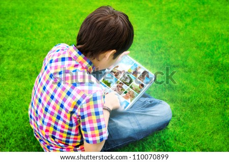 Little boy sitting on grass and using tablet computer to watch or share photo and video files - stock photo