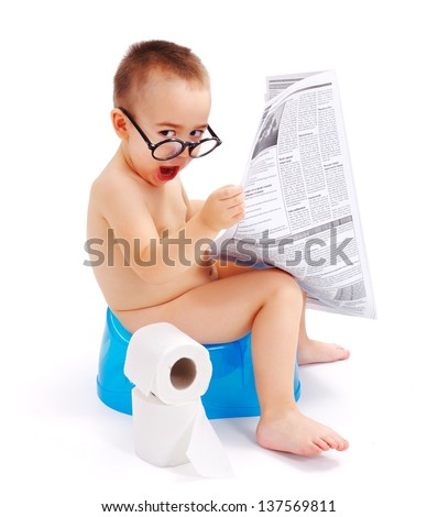 Little boy sitting on potty, wearing big glasses and holding newspaper - stock photo