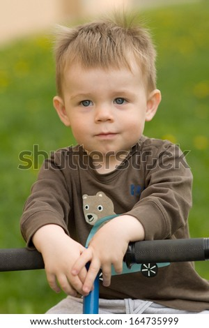 little boy sitting on seesaw