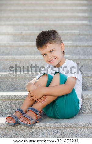 little boy sitting on stairs outdoor. Outdoors portrait of smart child boy