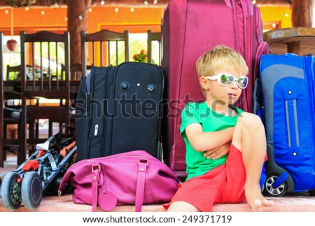 little boy sitting on suitcases ready to travel, travel concept - stock photo