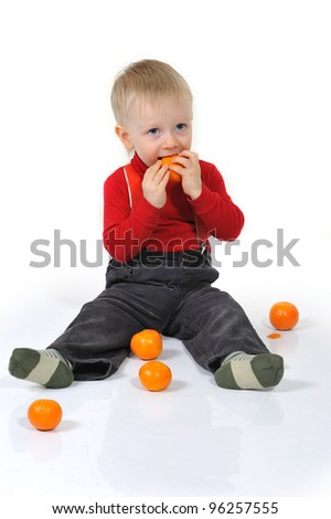 Little boy sitting on the floor and eat an orange