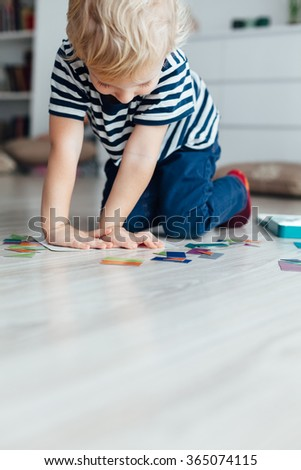 Little boy sitting on the floor and playing puzzle - stock photo