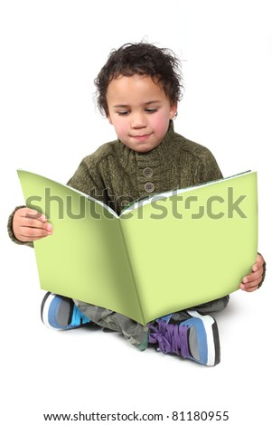 Little boy sitting on the floor reading a green book