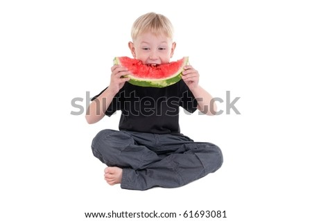Little boy sitting on the floor taking a big bite from a watermelon