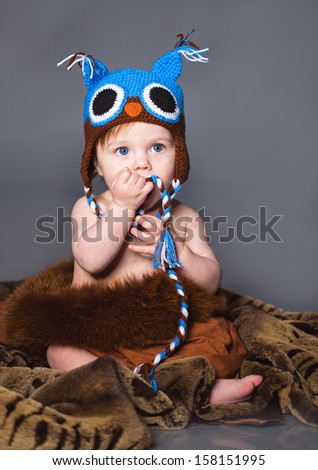 Little boy sitting on the fur in winter hat - stock photo