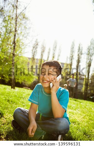 Little boy sitting on the grass and having phone conversation. - stock photo