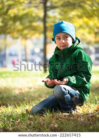 Little boy sitting on the grass in a cap and jacket and holding something in his hands