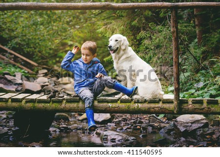 Little boy sitting on the wooden bridge with golden retriever and is throwing down stones into the river - stock photo