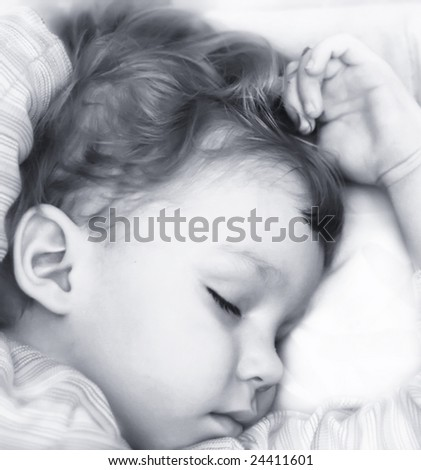 Little boy sleep on white bed. High key