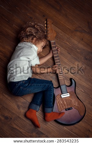 Little Boy Sleeping And Hugging Guitar - stock photo