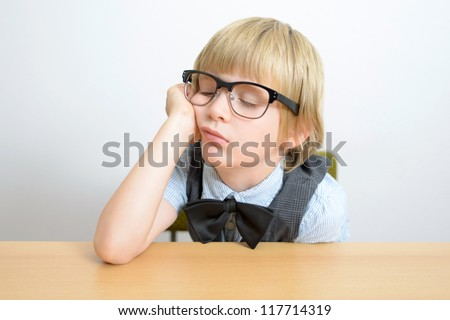 little boy sleeps at the office desk - stock photo