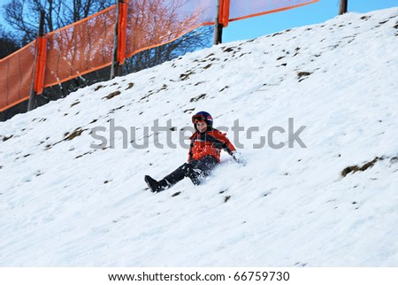 little boy sliding over the the snow hill