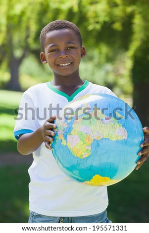 Little boy smiling at camera holding globe in the park on a sunny day
