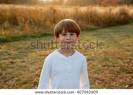 Little boy smiling for the camera at sunset - stock photo