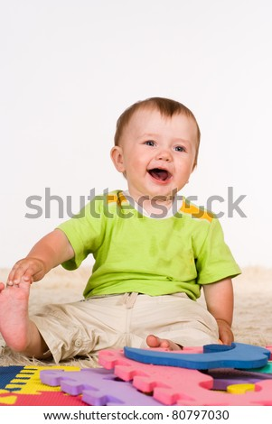 little boy smiling sitting on a carpet
