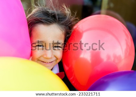 little boy smiling  with big colorful balloons - stock photo