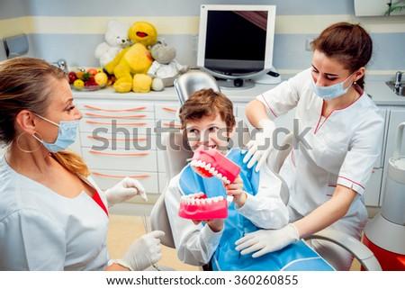 Little boy smiling with dentures, in the dental office.