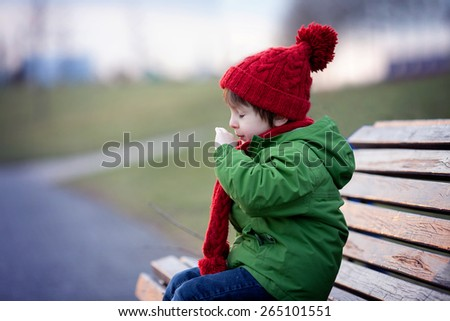 Little boy, sneezing and blowing his nose outdoor on a sunny winter day, sitting on a bench - stock photo
