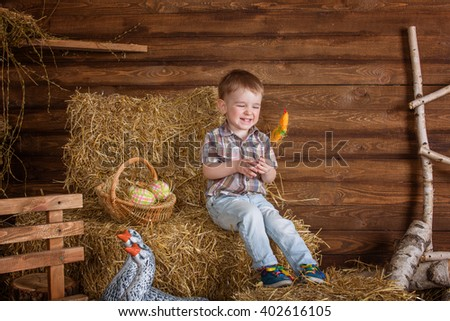 little boy son with rabbit and ducks sitting on the hay in bright clothes Easter, eggs, festive mood, emotion and smile surprise holiday celebration