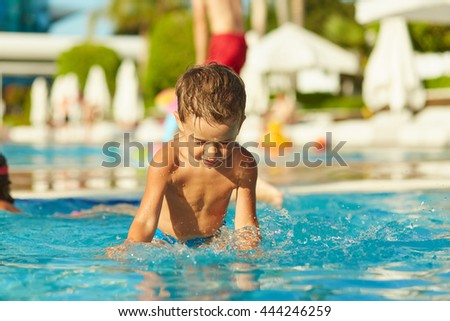 Little boy splashing water in swimming pool