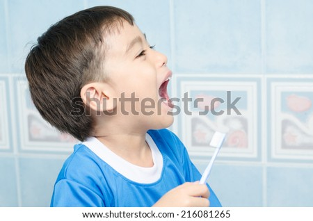 Little Boy squeezing toothpaste Teeth on white background - stock photo