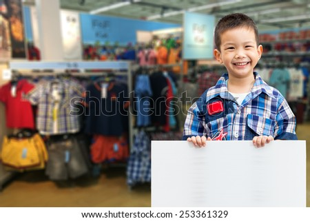 little boy standing and holding empty white board with kids shirt shop background