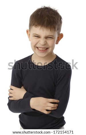 Little boy standing arms crossed showing his teeth, snarling, looking at camera. - stock photo