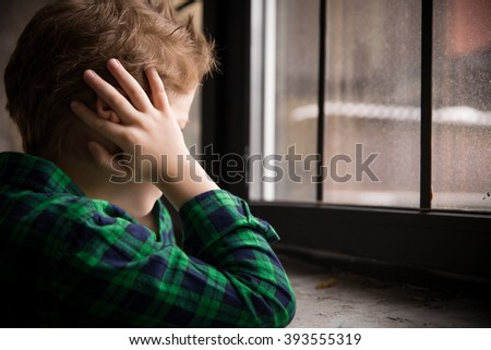 Little boy standing behind the window in sad mood. Sad Teenager looking in the Window and closing his ears with hands. Unhappy child in a plaid shirt. Alone at home. Upset. - stock photo
