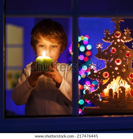 Little boy standing by window at Christmas time and holding candle. With colorful lights from Christmas tree on background, selective focus. Square size. - stock photo