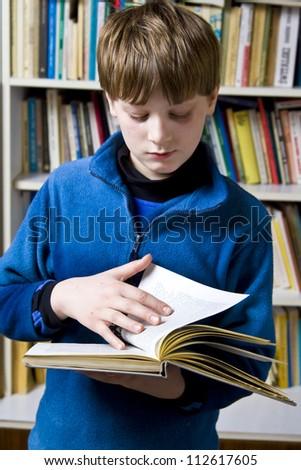 Little boy  standing near the bookshelf - stock photo