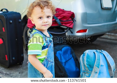 little boy standing near the car with backpacks - stock photo