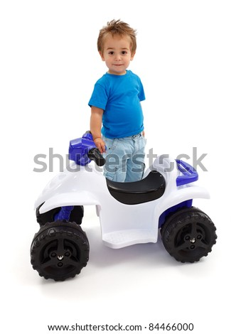 Little boy standing near toy off road quad