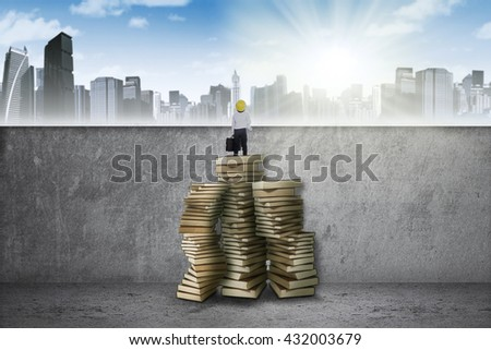 Little boy standing on a pile of books to see a town and get success