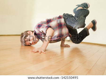 Little boy standing on both hands. Body almost horizontal - stock photo