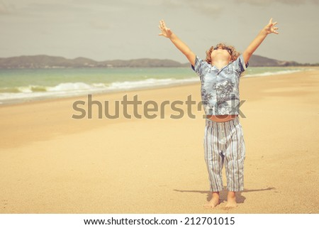 little boy standing on the beach at the day time - stock photo