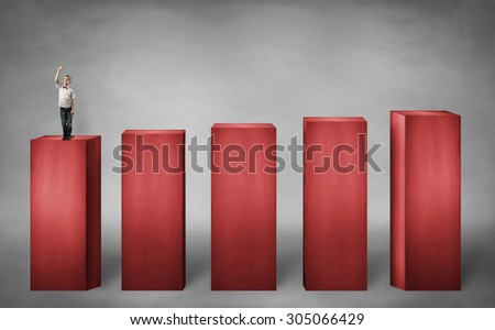 little boy standing on the lower stage holding pen and writing something - stock photo