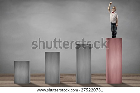 little boy standing on the top step holding pen and writing something - stock photo