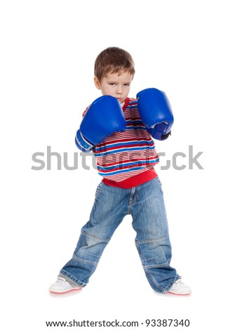 Little boy standing with blue boxing gloves, isolated on white - stock photo