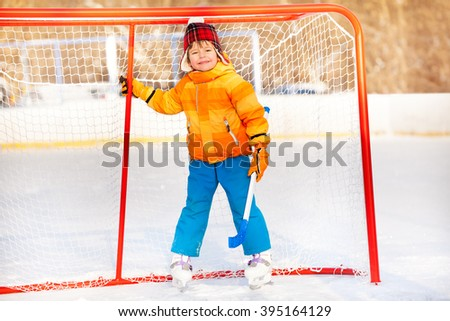 Little boy standing with hockey stick smiling - stock photo