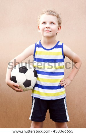 little boy stands with soccer ball,