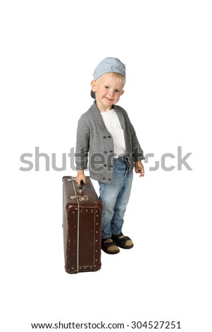 Little boy stands with vintage suitcase in hand isolated on white background - ready to travel - stock photo