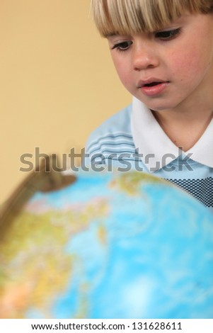 Little boy staring at globe - stock photo