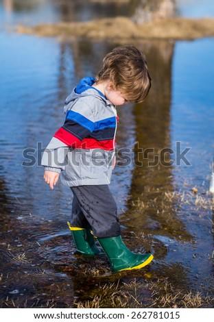Little boy strolling through puddles wearing rainboots. - stock photo