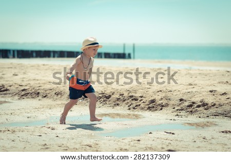 little boy surf dude is running through the sand and water on the beach - stock photo