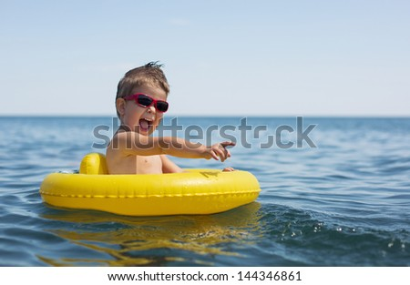Little boy swimming and playing at sea - stock photo