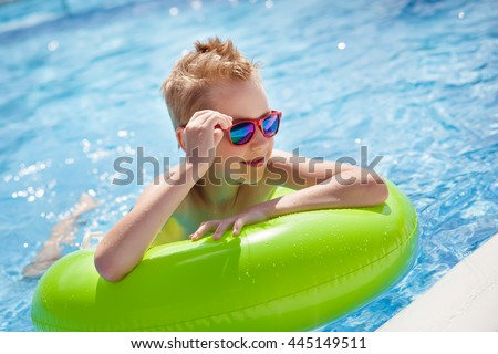 Little boy swimming in the pool with big bright green rubber ring, having fun in aquapark. - stock photo