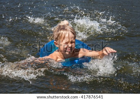 Little boy swims with inflatable ring in the sea - stock photo